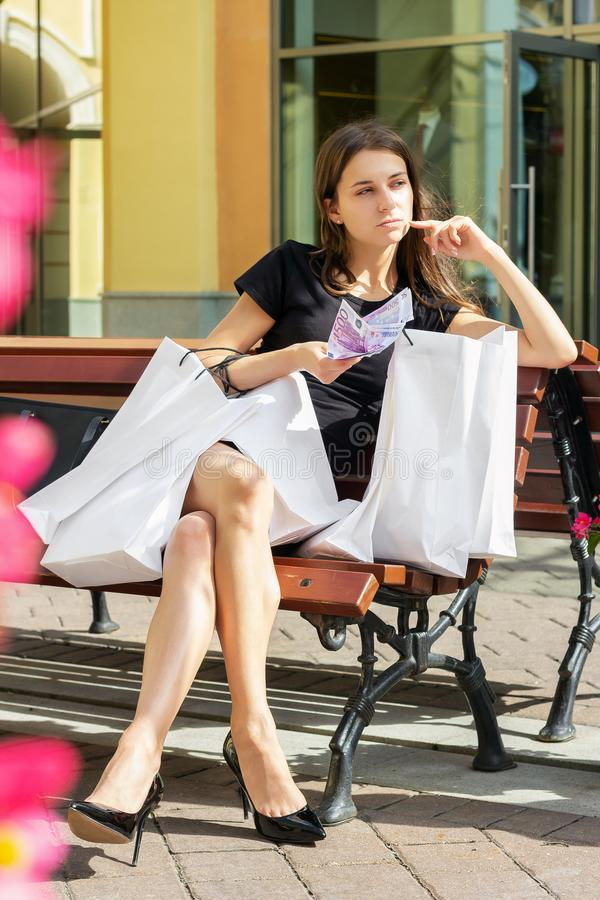Girl thinks what to spend money on shopaholic purchase stock photos