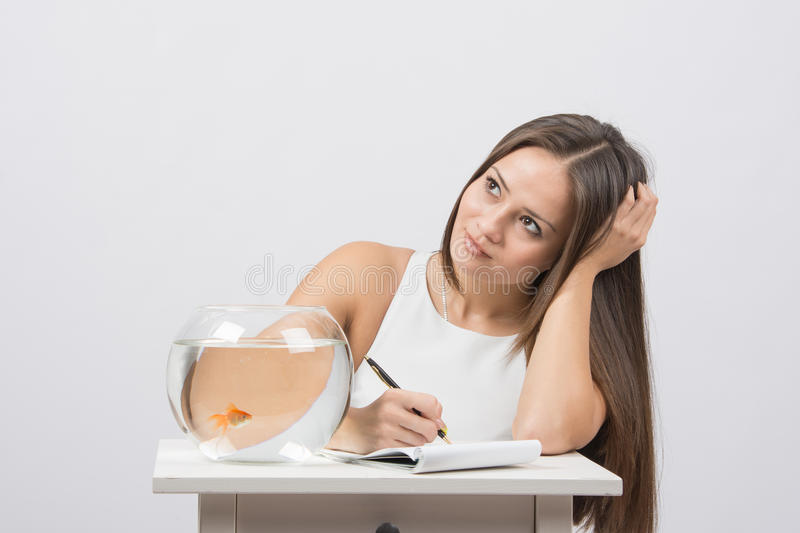 Girl thoughtfully writing in a notebook, standing next to an aquarium with goldfish. A young girl sits next to a round aquarium in which swimming goldfish stock image