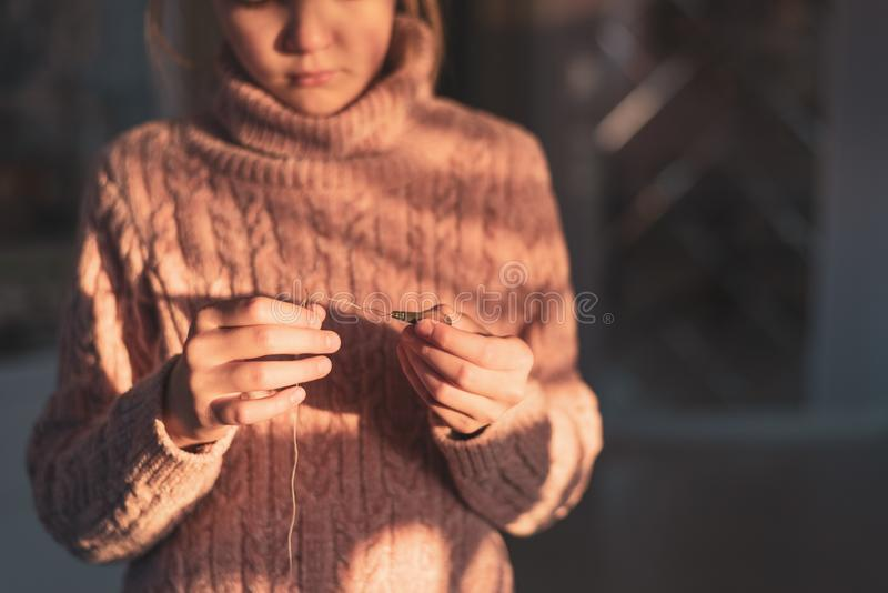 Girl threading needle with needle threader, simple repair of clothes. Close up hands  of young needlewoman stock photo