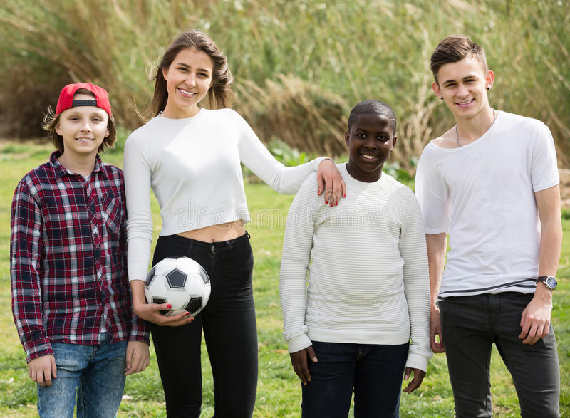 Girl and three boys playing football in spring park and smiling. Positive spanish girl and three boys playing football in spring park and smiling royalty free stock photos