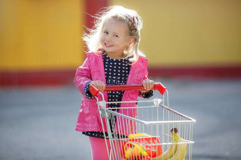 Girl three years old with a shopping trolley and paper bags in the parking lot near the supermarket. stock photos