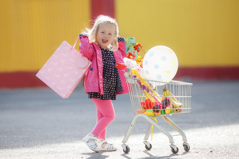 Girl three years old with a shopping trolley and paper bags in the parking lot near the supermarket. royalty free stock images