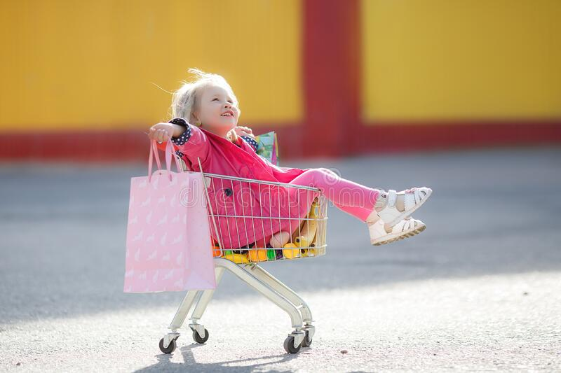 Girl three years old with a shopping trolley and paper bags in the parking lot near the supermarket. stock images