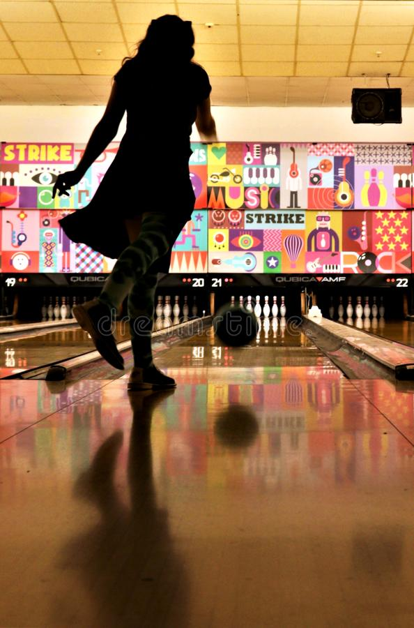 Girl throwing a bowling ball. Teenage girl gracefully throws a bowling ball down the lane at a bowling alley in Germany stock photography