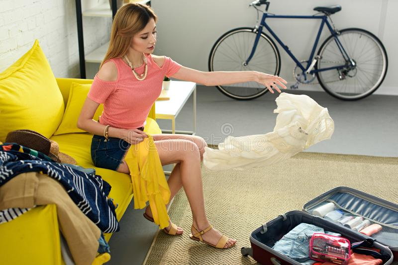 girl throwing clothes into suitcase royalty free stock photo
