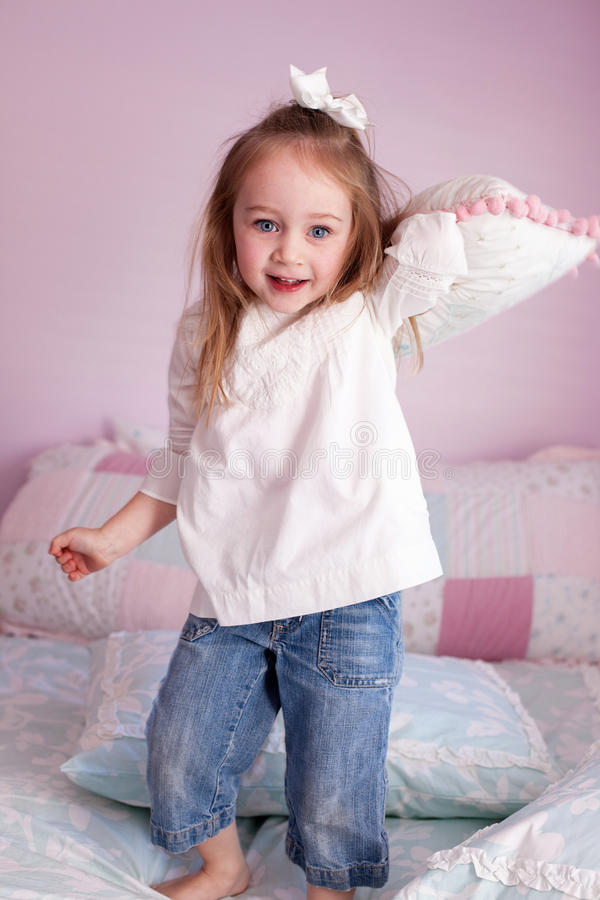 Download Girl throwing a pillow stock photo. Image of bedroom - 14064112