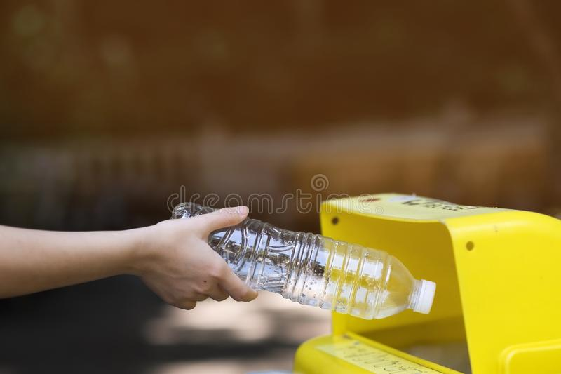 The girl is throwing plastic bottles into the trash for recycling stock photos