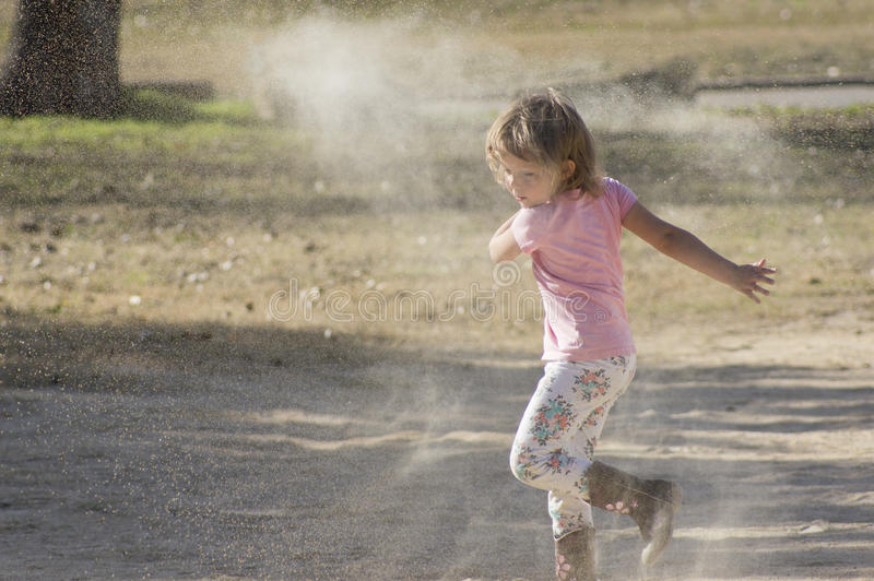 Girl Throwing Sand. Little girl throwing sand and playing outside royalty free stock photos