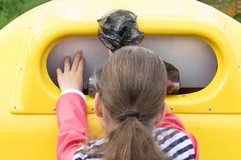 Girl throws a bag of plastic trash in a special container, rear view stock images
