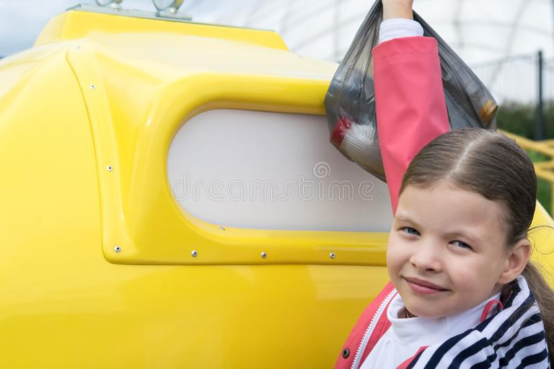 Girl throws a black bag with waste into a special yellow container. Girl throws a black bag with waste into  a special yellow container royalty free stock photography