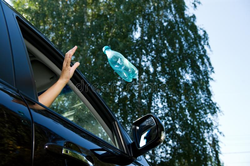 A girl throws an empty plastic bottle into the open window of a car. A flying object is slightly blurred, enhancing the stock photography