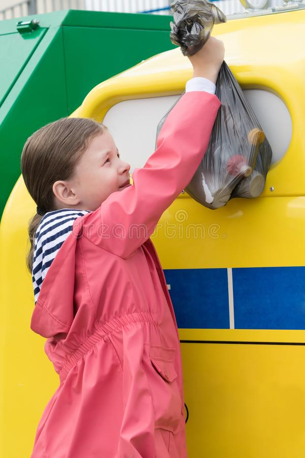 Girl throws a large black bag with trash in a yellow container. Girl throws a large black bag with trash  in a yellow container stock photo