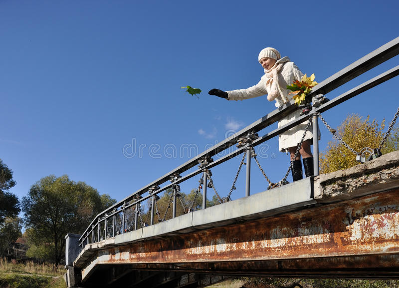 Girl Throws Maple Sheet To The Water From Bridge Royalty Free Stock Image