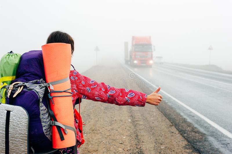 Girl with thumb-up hitchhiking on a suburb road. In the fall stock photo