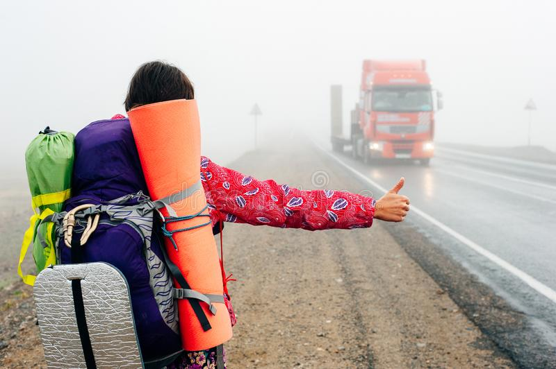 Girl with thumb-up hitchhiking on a suburb road. In the fall stock image
