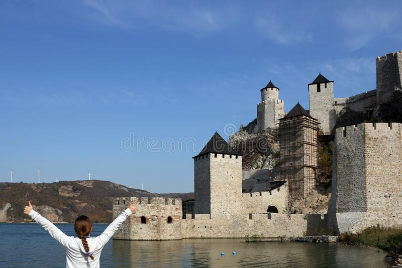 Girl with thumbs up looks at the Golubac fortress stock images