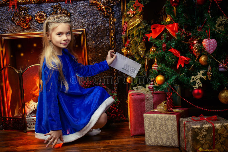 Girl in tiara. Beautiful eight year old girl in a blue dress and a tiara like a Snow Maiden standing near the Christmas tree. Beautiful Christmas decoration royalty free stock images