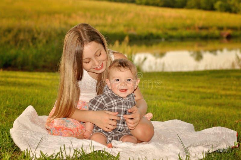 Girl tickling baby on blanket stock photos