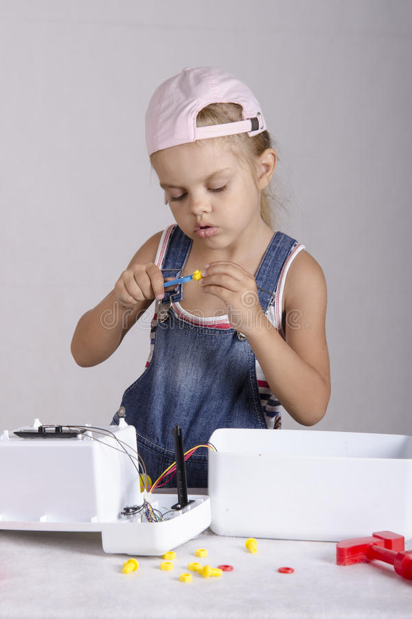 Girl tighten the screws to wrench, repairing toy royalty free stock images