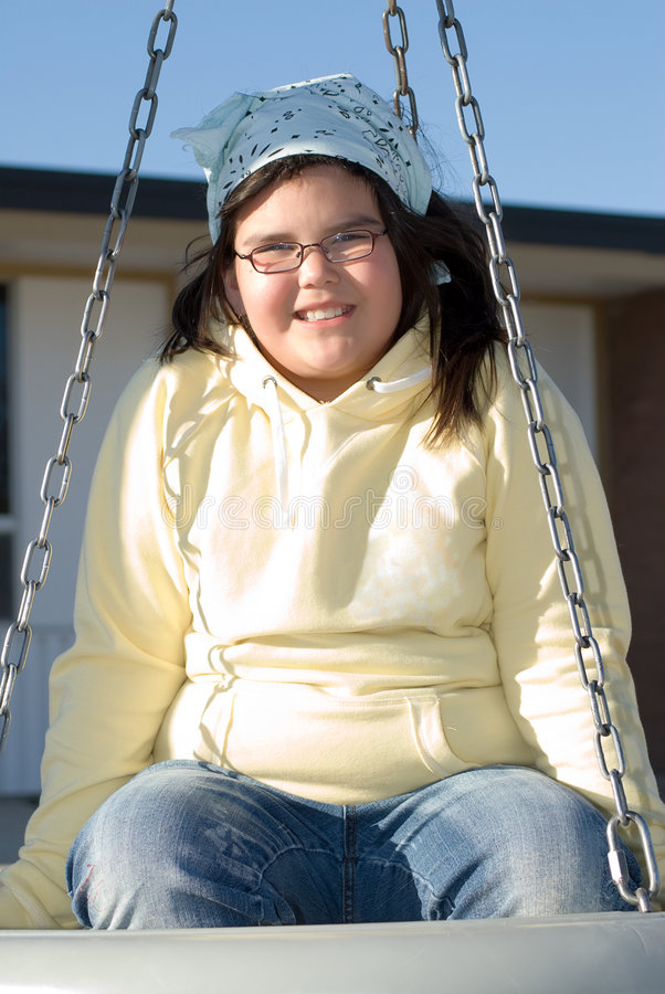 Girl On Tire Swing. A young girl with glasses, swinging on a tire swing royalty free stock images