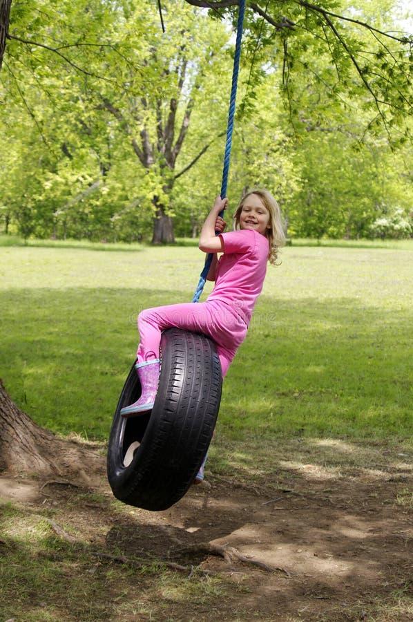 Girl on tire swing. Girl in pink on tire swing