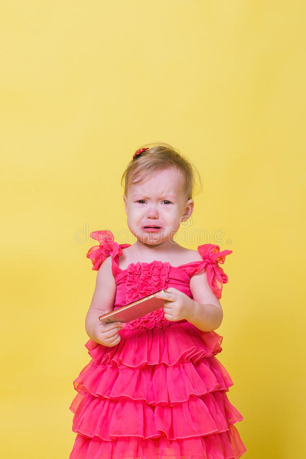 Girl toddler in a pink dress on a yellow background holding a smartphone and crying.  stock photos