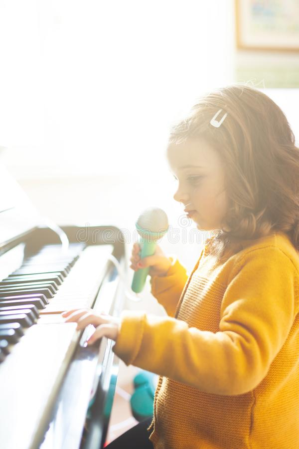 Girl toddler plays with piano and toy microphone royalty free stock images