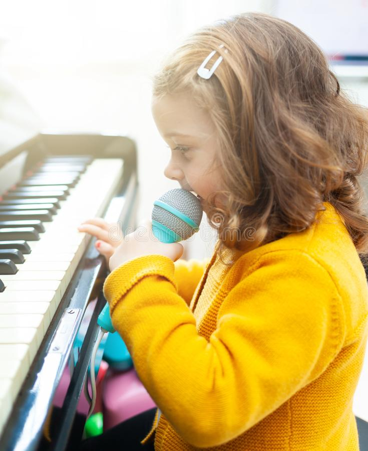 Girl toddler plays with piano and toy microphone stock image