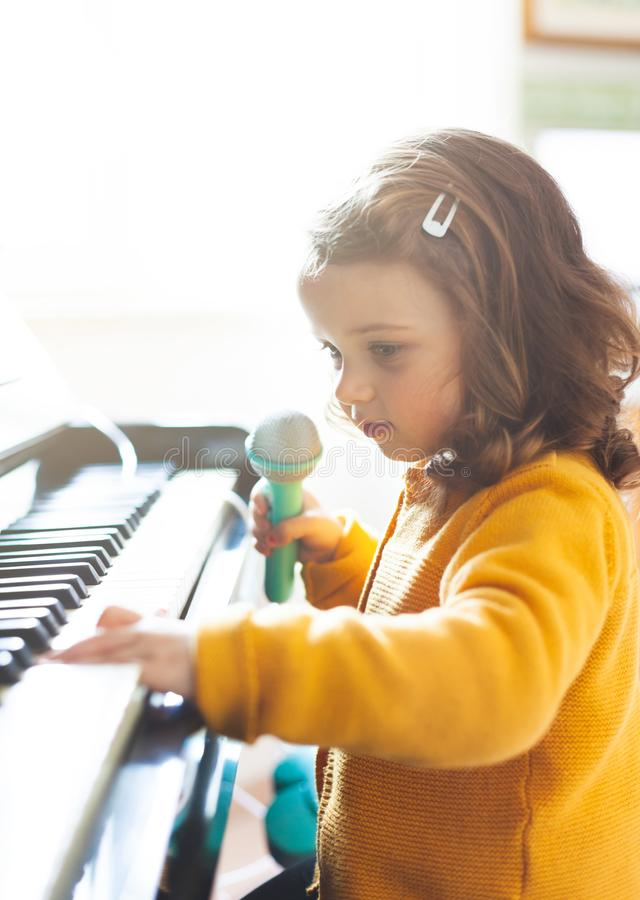 Girl toddler plays with piano and toy microphone stock photos