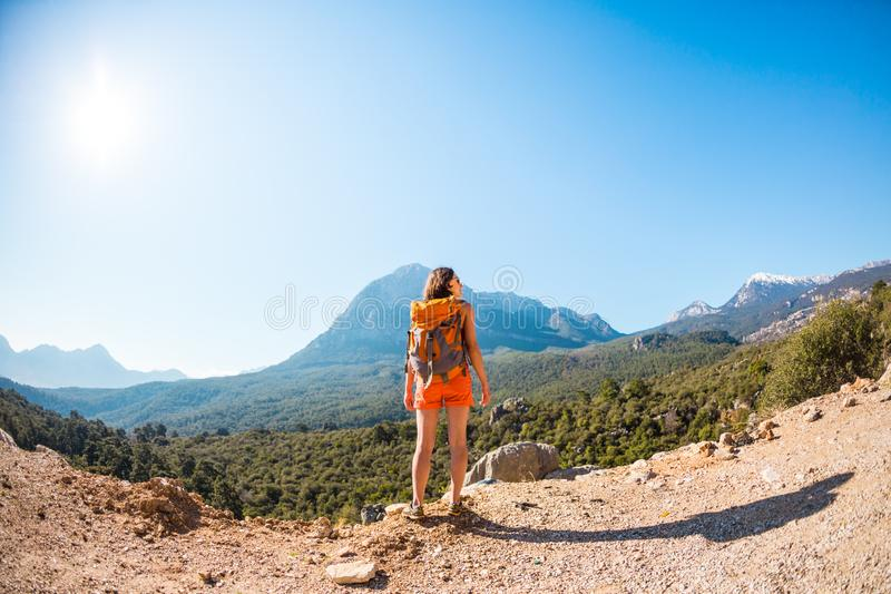 Girl at the top of the mountain. A woman with a backpack walks along a mountain path. Climb to the top. Travel to picturesque places. Tourist against the sky royalty free stock photos