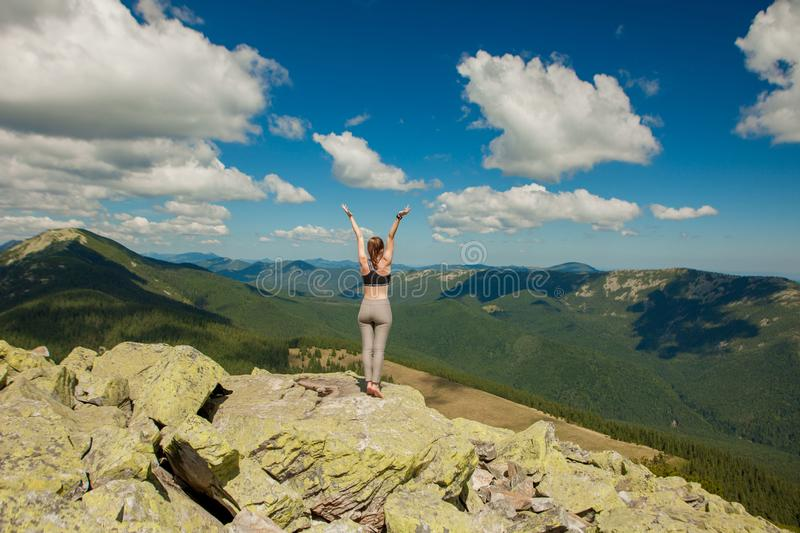 The girl at the top of the mountain raised her hands up. Wide summer mountain view at sunrise and distant mountain range covered. stock images