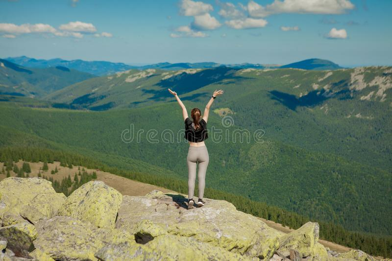The girl at the top of the mountain raised her hands up. Wide summer mountain view at sunrise and distant mountain range covered. royalty free stock photos