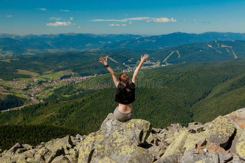 The girl at the top of the mountain raised her hands up. Wide summer mountain view at sunrise and distant mountain range covered. royalty free stock images