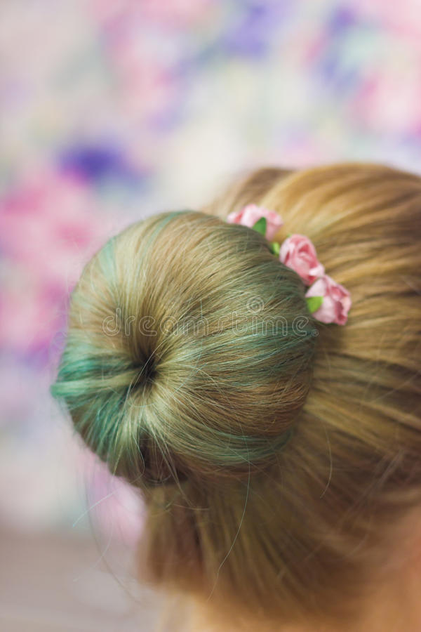 Girl with topknot with hairpins. Women nape with hairstyle topknot green colored hair and hairpins with pink roses in it close-up shallow depth of field on pink royalty free stock photos