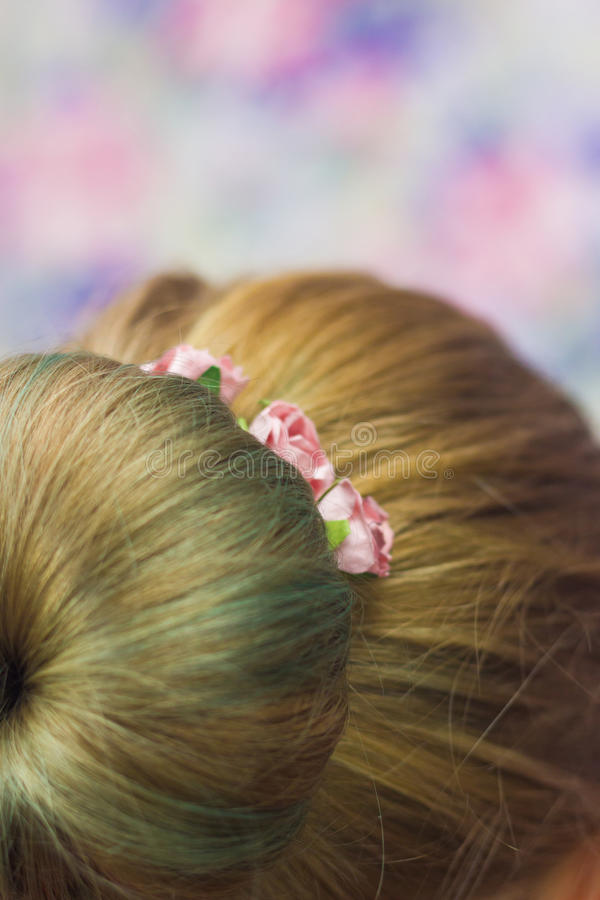 Girl with topknot on nape. Women nape with hairstyle topknot green colored hair and hairpins with pink roses in it close-up shallow depth of field on pink stock photos