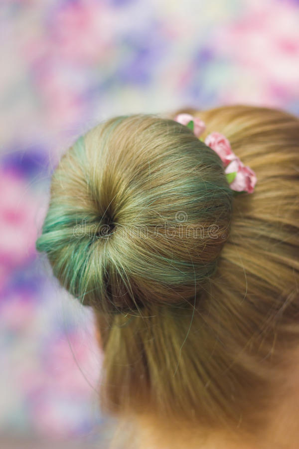 Girl with topknot on nape. Women nape with hairstyle topknot green colored hair and hairpins with pink roses in it close-up shallow depth of field on pink royalty free stock image