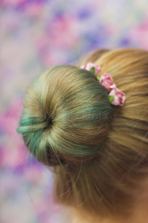 Girl with topknot. Women nape with hairstyle topknot green colored hair and hairpins with pink roses in it close-up shallow depth of field on pink background royalty free stock photo