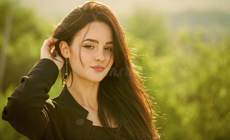 Girl touch long brunette hair on natural landscape. Woman with makeup face on sunny day. Skin care, youth, health concept. Fashion, vogue, style. Beauty stock image