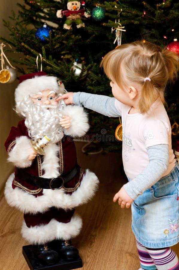 Girl Touching Santa Claus Royalty Free Stock Photography