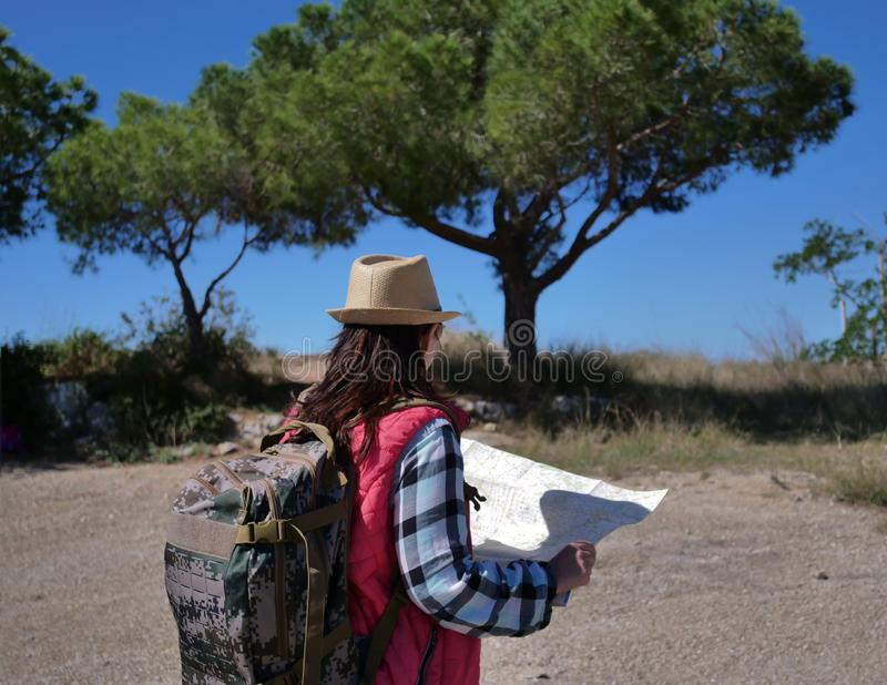 Girl tourist with a backpack and a map on nature, back view royalty free stock images