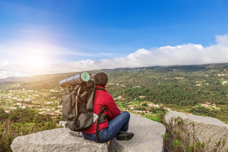 Girl tourist with a backpack resting in a campaign. stock image