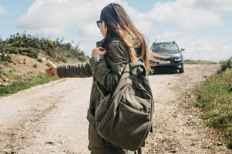 Girl tourist with a backpack travels hitchhiking. She raised her finger up and tried to stop the car to continue her journey stock photos