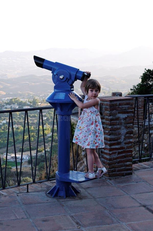 Girl tourist binoculars. A young, preschool girl standing near tourist binoculars at a scenic overlook stock photo