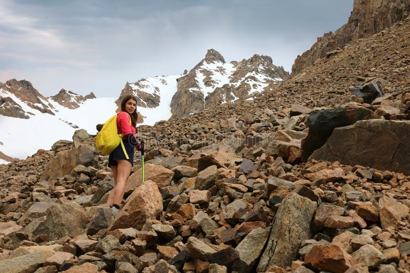 Girl tourist climbs the rocky slope of the mountain royalty free stock photos