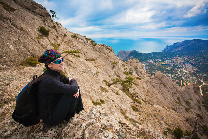 Girl tourist enjoys the view from the mountain top. Tourist enjoys the view from the mountain top royalty free stock image