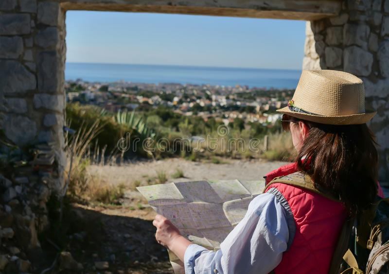 A girl tourist in a hat stands with a map of the area stands in front of a stone old gate, rear view stock photos