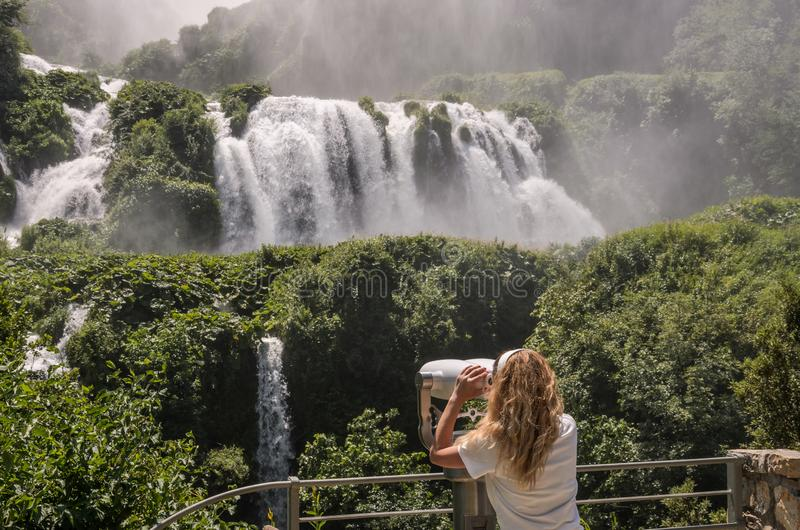 Girl tourist looks through binoculars at a waterfall Cascata delle Marmore in Italy royalty free stock photography