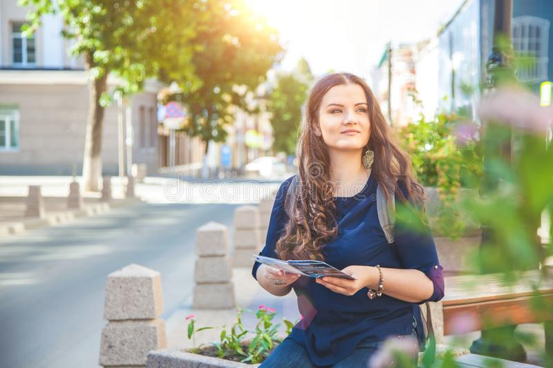 Girl tourist with map in hand on a city street Tourists concept. Exploring the city. royalty free stock photography