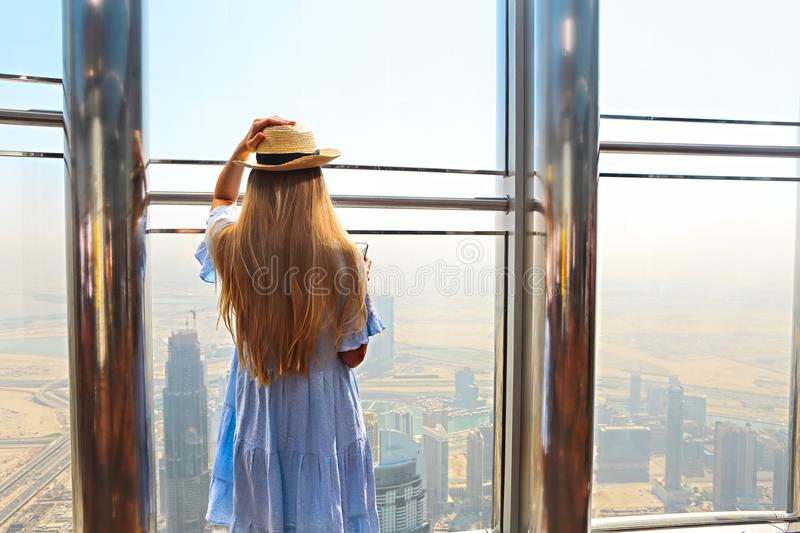 Girl tourist with mobile phone by the window of skyscraper of th royalty free stock images
