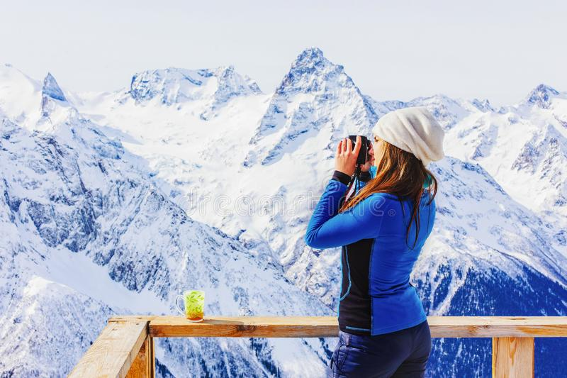 Girl tourist with photo camera on a background of mountains stock images